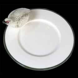 Perdrix blanche sur le bord d'une petite assiette à pain